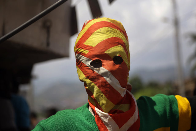 A masked Protester waits for  police during clashes in the Nyakabyga neighborhood of Bujumbura, Burundi, Thursday May 21, 2015. (Photo by Jerome Delay/AP Photo)
