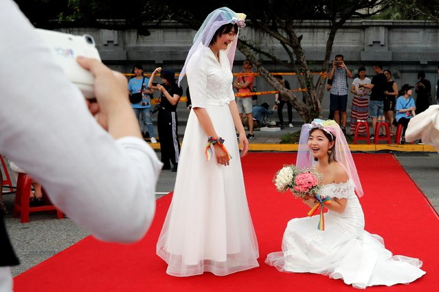 Lesbian newlyweds in wedding dresses pose during a mass wedding banquet, one day after same-s*x marriage officially became legal, in Taipei, Taiwan on May 25, 2019. (Photo by Tyrone Siu/Reuters)