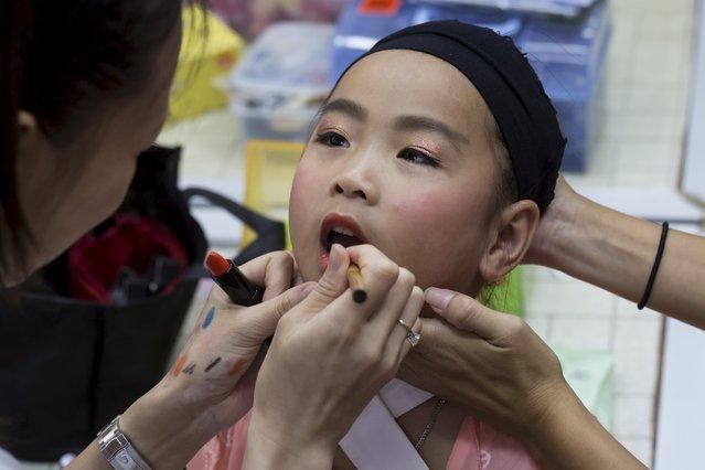 Peony Chu, a five-year-old, receives make up before she takes part in a Bun Festival parade at Hong Kong's Cheung Chau island, China May 25, 2015. (Photo by Tyrone Siu/Reuters)