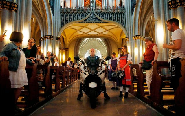 A motorcyclist from Switzerland arrives with his motorcycle to attend a Blessing of the Bikes service at the Cathedral St-Nicolas, on June 23, 2019 in Fribourg. (Photo by Stefan Wermuth/AFP Photo)