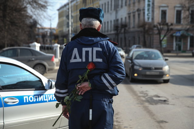 A traffic policeman hides a rose behind his back before giving it to a female driver ahead of International Women's Day in Ryazan, Russia on March 7, 2017. (Photo by Alexander Ryumin/TASS via Getty Images)