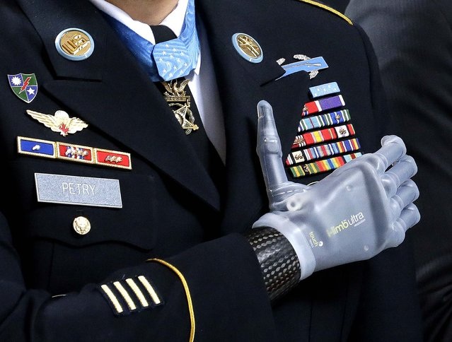"Medal of Honor recipient Sgt. 1st Class Leroy Petry stands with his prosthetic hand over his heart and wears his Medal of Honor during the ""Pledge of Allegiance"" at the Capitol in Olympia, Wash., during a ceremony to honor Petry and other recipients of the Medal of Honor who are from Washington state, on April 2, 2014. (Photo by Ted S. Warren/Associated Press)"
