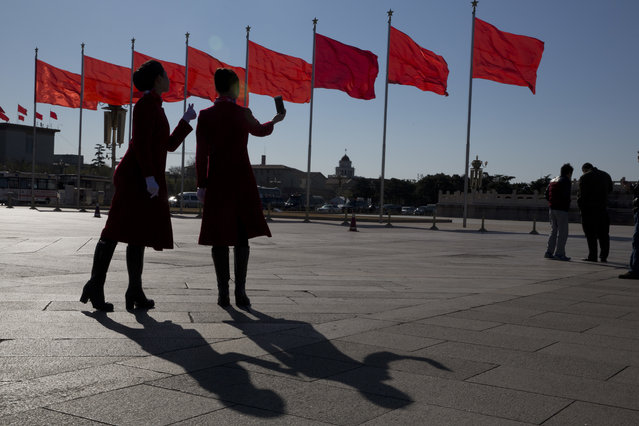 In this photo taken Sunday, March 12, 2017, hospitality staff members pose for a selfie near the Great Hall of the People where a plenary session of the National People's Congress is held in Beijing, China. (Photo by Ng Han Guan/AP Photo)