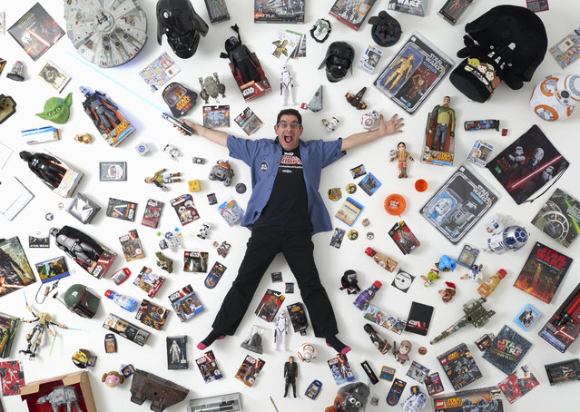 """Star Wars collector James Burns, 44, poses for a photograph with some of his collection in London December 2, 2015. He said """"I've met so many wonderful people, all over the world. It's a wonderful community of like-minded people with an interest in Star Wars. There's nothing else like it"""". (Photo by Paul Hackett/Reuters)"""