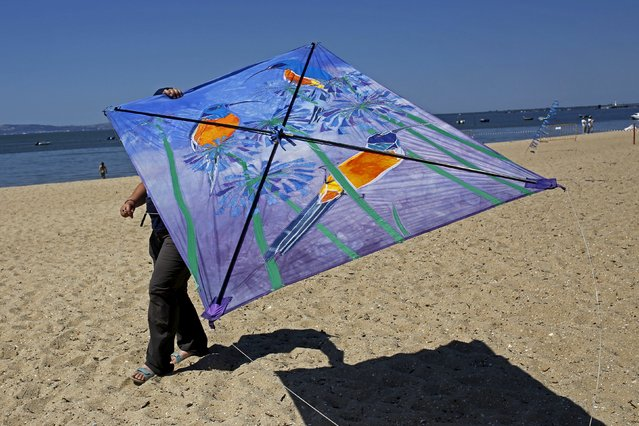 A woman flies a kite during the 13th International Kite Festival at the Moinhos beach in Alcochete near Lisbon, Portugal, June 28, 2015. (Photo by Hugo Correia/Reuters)