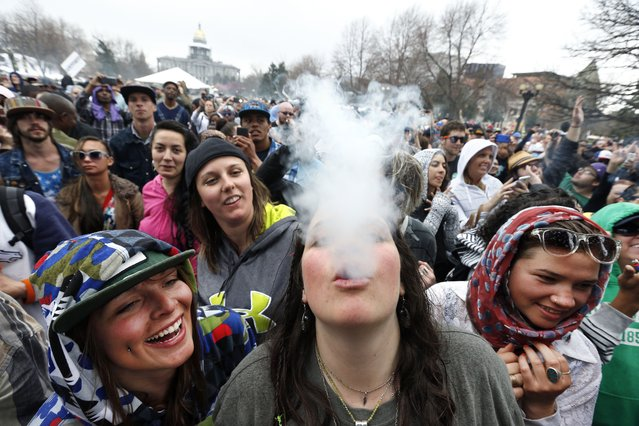 With the Colorado state capitol building visible in the background, partygoers dance and smoke pot on the first of two days at the annual 4/20 marijuana festival in Denver, Saturday April 19, 2014. The annual event is the first 420 marijuana celebration since retail marijuana stores began selling in January 2014. (Photo by Brennan Linsley/AP Photo)