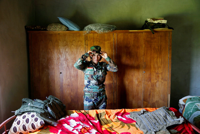 Yazidi female fighter Asema Dahir, 21, adjusts her cap inside a bedroom at a site near the frontline of the fight against Islamic State militants in Nawaran near Mosul, Iraq April 20, 2016. (Photo by Ahmed Jadallah/Reuters)