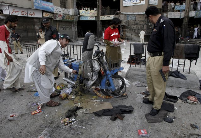 Security officials and rescue workers check the site of a bomb blast in Quetta, Pakistan, July 5, 2015. According to local media, a bomb planted in a parked motorcycle exploded, killing one person and injuring 15, including three women and two children at Bacha Khan Chowk in Quetta on Sunday. (Photo by Naseer Ahmed/Reuters)