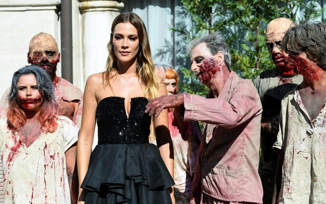 """Cast member Martina Troni poses next to people dressed as zombies during the screening of the documentary """"Fulci for Fake"""" on September 3, 2019 durind the 76th Venice Film Festival in Venice, Italy. (Photo by Piroschka van de Wouw/Reuters)"""