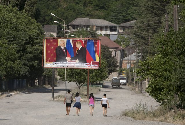 People walk near a billboard, showing President of the breakaway region of South Ossetia Leonid Tibilov during a meeting with Russian President Vladimir Putin, in Leningori (or Akhalgori), in the breakaway region of South Ossetia, Georgia, July 6, 2015. (Photo by Kazbek Basaev/Reuters)