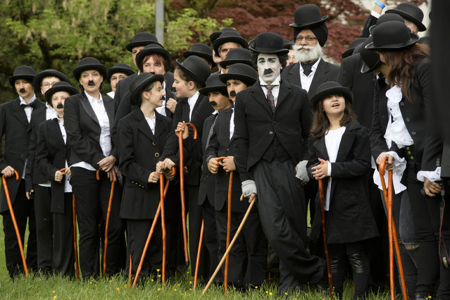 """Some 662 people dressed as """"The Tramp"""" pose for a group picture to mark the first anniversary of Chaplin's World By Grevin, and Charlie Chaplin's birthday, as the museum plans to set the record for the worl's largest gathering of people dressed as The Tramp, on April 16, 2017 in Corsier-sur-Vevey. Chaplins World, a large-scale museum dedicated to Charlie Chaplin and his lifes work is located in the Manoir de Ban and its park where Chaplin and his family lived through 1952 -1977. (Photo by Richard Juilliart/AFP Photo)"""