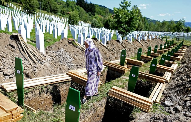 A woman searches the grave of her relative among 136 newly identified victims of the 1995 Srebrenica massacre lined up for a joint burial in Potocari, Bosnia and Herzegovinain Memorial center Potocari, Bosnia and Herzegovina July 10, 2015. (Photo by Dado Ruvic/Reuters)