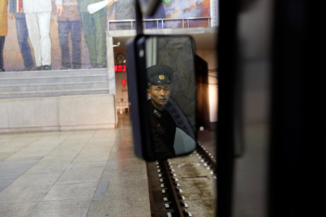 A railway worker is reflected in a mirror as a train leaves a subway station visited by foreign reporters in central Pyongyang, North Korea on April 14, 2017. (Photo by Damir Sagolj/Reuters)