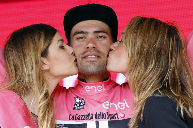 Two hostesses kiss Dutch cyclist Tom Dumoulin of Giant – Alpecin team as he bears the leader's pink jersey on the podium in the 7th stage of 99th Giro d'Italia, Tour of Italy, from Sulmona to Foligno of 211 km on May 13, 2016 in Foligno, Italy. (Photo by Luk Benies/AFP Photo)