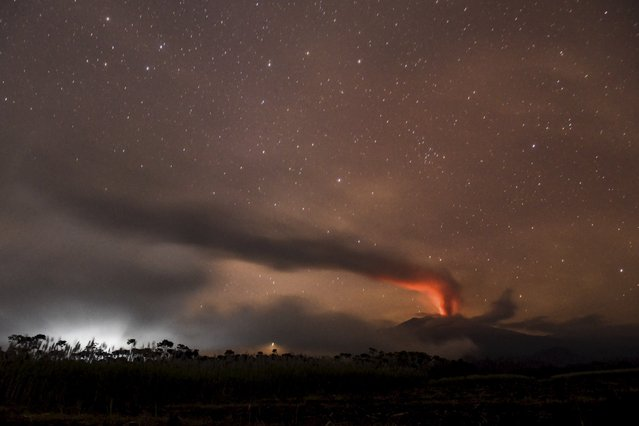 Volcanic ash and clouds are illuminated by lava from the crater of Mount Raung as seen from  Songgon, Banyuwangi East Java, Indonesia on July 11, 2015 in this photo taken by Antara Foto. Indonesian authorities reopened the main airport on the popular resort island of Bali on Saturday after its closure on Friday due to a volcanic eruption on nearby Java island, an airport official said. (Photo by Zabur Karuru/Reuters/Antara Foto)