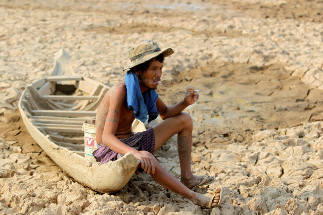 A fisherman sits to smoke on his boat at a Bak Angrout dried up pond at the drought-hit Kandal province in Cambodia May 13, 2016. (Photo by Samrang Pring/Reuters)