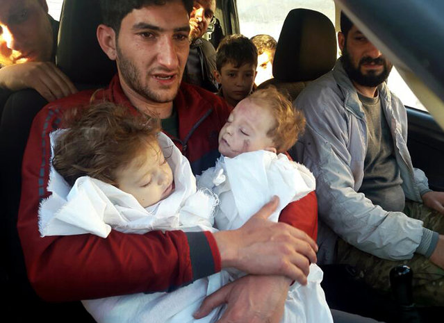 In this picture taken on Tuesday April 4, 2017, SAbdul-Hamid Alyousef, 29, holds his twin babies who were killed during a suspected chemical weapons attack, in Khan Sheikhoun in the northern province of Idlib, Syria. Alyousef also lost his wife, two brothers, nephews and many other family members in the attack that claimed scores of his relatives. The death toll from a suspected chemical attack on a northern Syrian town rose to 72 on Wednesday as activists and rescue workers found more terrified survivors hiding in shelters near the site of the harrowing assault, one of the deadliest in Syria's civil war. (Photo by Alaa Alyousef via AP Photo)