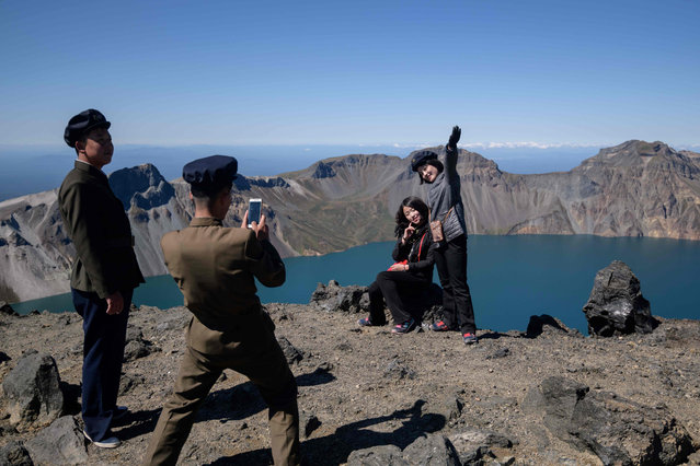 In a photo taken on September 11, 2019, North Korean students pose for photos as they march to the summit of Mount Paektu, near Samjiyon. Mount Paektu has long been considered the spiritual birthplace of the Korean nation and is a place of pilgrimage for tens of thousands of North Koreans every year, who are trained from birth to revere their leaders. Every year 100,000 North Koreans or more are taken on study tours to the camp, the mountain, and nearby revolutionary sites where relics of operations are preserved. Dressing in khaki uniforms said to resemble guerrillas' outfits and carrying red flags, they march to the summit of the volcano. (Photo by Ed Jones/AFP Photo)