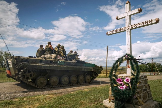 Russia-backed separatist APC rides by an Orthodox cross with a sign reading Save and Guard, with a memorial to the victims of the Malaysian Airlines MH17 plane crash, in the back, near the village of Hrabove, eastern Ukraine, Thursday, July 16, 2015. (Photo by Mstyslav Chernov/AP Photo)