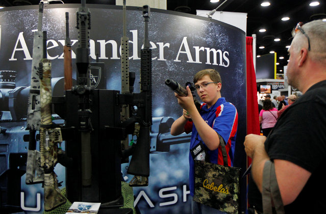 Blaine Bushnell (13) and his father Justin look over Alexander Arms guns at the National Rifle Association's annual meetings & exhibits show in Louisville, Kentucky, May 21, 2016. (Photo by John Sommers II/Reuters)