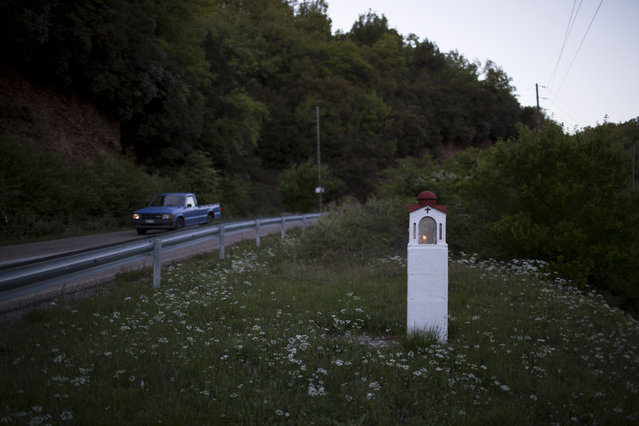 In this photo taken on Wednesday, April 26, 2017, a candle is lit in a roadside shrine near the village of Lalas, in the Peloponnese region of southern Greece. (Photo by Petros Giannakouris/AP Photo)