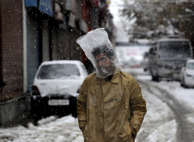 A Kashmiri man cover his head with plastic bag as it snows in Srinagar, Indian controlled Kashmir, Thursday, November 7, 2019. The region received its first snow on Wednesday, bringing temperatures down drastically and affecting air and vehicular traffic. (Photo by Mukhtar Khan/AP Photo)