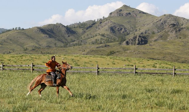 A Khakas equestrian rides a horse during the reconstruction of daily life and traditional holidays celebrated by indigenous population of the Republic of Khakassia during a demonstration for visitors at a museum preserve outside Kazanovka village, southwest of the city of Abakan, Russia, July 24, 2015. (Photo by Ilya Naymushin/Reuters)