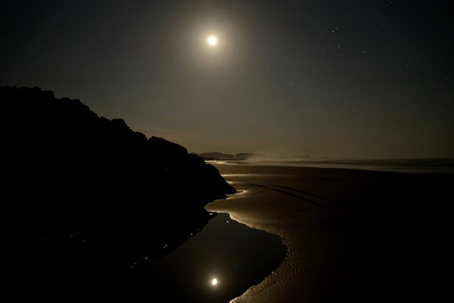 """""""Moonligth in paradise"""". One day after the red moon eclipse. Quiet warm night at the beach reflected wirh the moon reflected on ponds with soft light inviting to meditate and enjoy the moment. Photo location: San Miguel Beach, Guanacaste, Costa Rica. (Photo and caption by Hernan Hernandez/National Geographic Photo Contest)"""