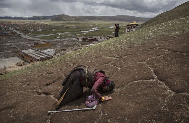 A Tibetan nomad woman prays on the 15th day of Saka Dawa, the holiest day of the Buddhist calendar when it is prohibited from harvesting, on May 21, 2016 at the  Sershul Monastery on the Tibetan Plateau in the Garze Tibetan Autonomous Prefecture of Sichuan province. (Photo by Kevin Frayer/Getty Images)