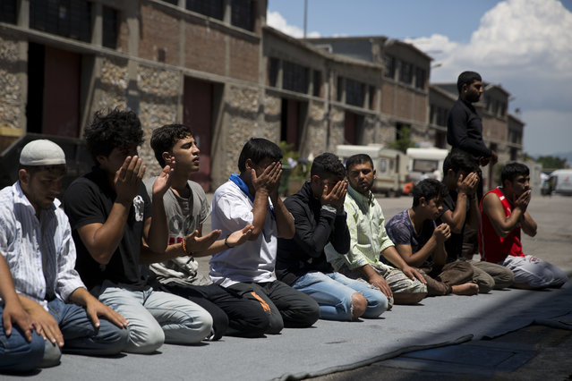 Afghan migrants stranded in Greece, pray on a dock at the port of Piraeus, near Athens on the first day of the holy fasting month of Ramadan, Monday, June 6, 2016. (Photo by Petros Giannakouris/AP Photo)