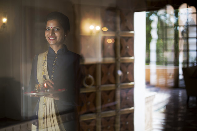 """""""Welcome to India"""". The beauty of India is boundless and penetrates every facet of the country. I captured this portrait in Jaipur as this beautiful young lady welcomed as into a hotel. I shot this through the glass of the front door to create a spiritual feeling to the image. She did the rest. India is one of the most welcoming places I have ever been. Photo location: Jaipur, India. (Photo and caption by Ryan Rapaport/National Geographic Photo Contest)"""
