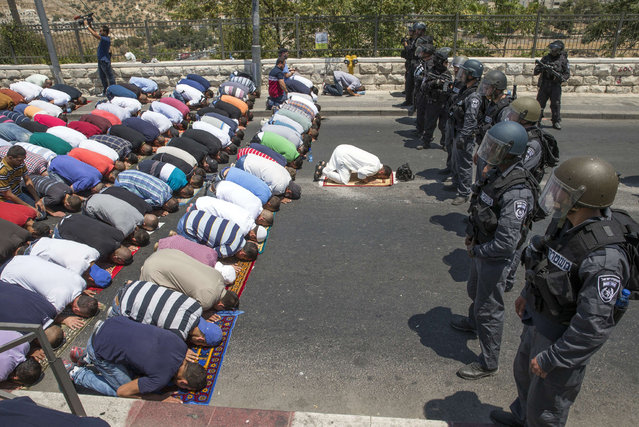 Guarded by Israeli policemen, Muslim worshipers pray on the streets of the Wadi al-Joz neighborhood in east Jerusalem on July 31, 2015, following restrictions by Israeli police to only allow men above 50-year-old to access the Al-Aqsa Mosque compound. (Photo by Jack Guez/AFP Photo)