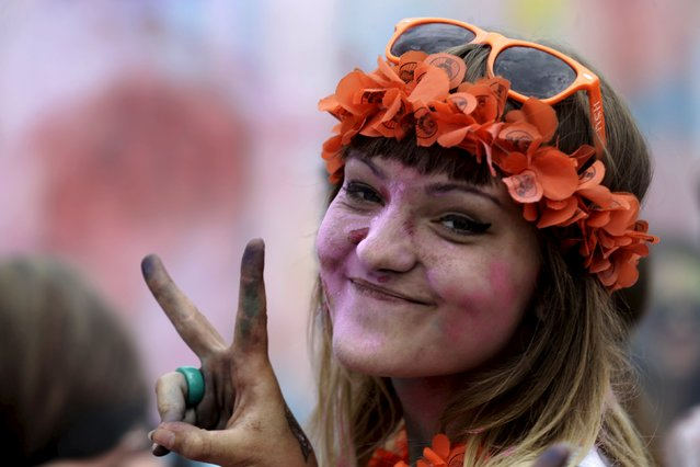 A woman reacts to the camera during the Holi festival, or the Festival of Colors, in Riga, Latvia, August 1, 2015. Primarily observed in India, the ancient Hindu religious festival has spread to other regions of the world. (Photo by Ints Kalnins/Reuters)