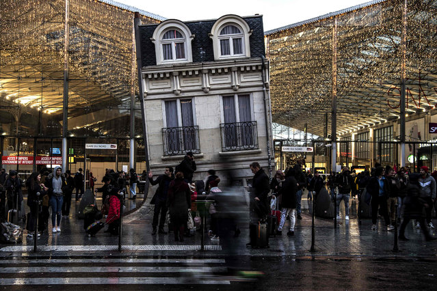 """Commuters stand outside Gare du Nord train station and by the piece of art """"Maison fond"""" (The melting house) by Argentinian artiste Leandro Erlich, in Paris on December 13, 2019, during a strike of Paris' public transports operator RATP and of the French state railway company SNCF employees over French government's plan to overhaul the country's retirement system. (Photo by Christophe Archambault/AFP Photo)"""