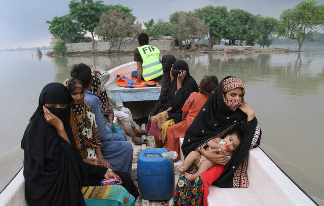 Pakistani volunteers rescue villagers from a flooded area in Layyah, Pakistan, Saturday, July 25, 2015. Heavy monsoon rains lashed an already-deluged northern Pakistan before dawn Saturday, as rescuers found the bodies of another 24 people killed by the flooding inundating parts of the country, police said. (Photo by Asim Tanveer/AP Photo)