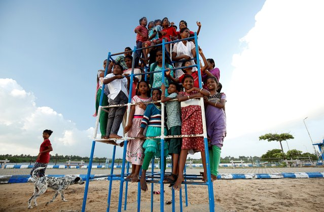Children staying in the care home set up by Karibeeran Paramesvaran and his wife Choodamani after they lost three children in the 2004 tsunami, pose in a park along a beach in Nagapattinam district in the southern state of Tamil Nadu, India, December 4, 2019. (Photo by P. Ravikumar/Reuters)