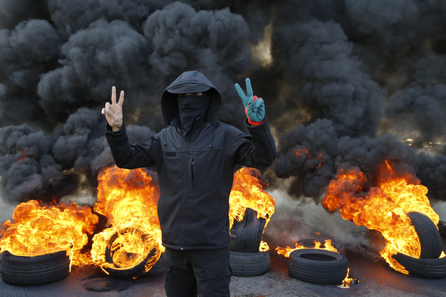 An anti-government protester flashes the victory sign as burning tires block a main highway during a protest in the town of Jal el-Dib, north of Beirut, Lebanon, Tuesday, January 14, 2020. Following a brief lull, Lebanese protesters returned to the streets, blocking several roads around the capital, Beirut, and other areas of the country on Tuesday in renewed rallies against a ruling elite they say has failed to address the economy's downward spiral. (Photo by Bilal Hussein/AP Photo)