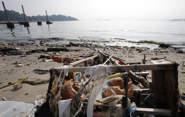 A toy doll is seen on Fundao beach in the Guanabara Bay in Rio de Janeiro March 13, 2014. (Photo by Sergio Moraes/Reuters)