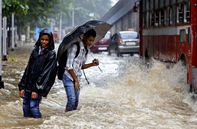 Indian boys walk in knee-deep water as it rains in Mumbai, India, Wednesday, July 9, 2014. Waterlogging caused by incessant rainfall disrupted road traffic in several areas on the commercial capital. (Photo by Rajanish Kakade/AP Photo)