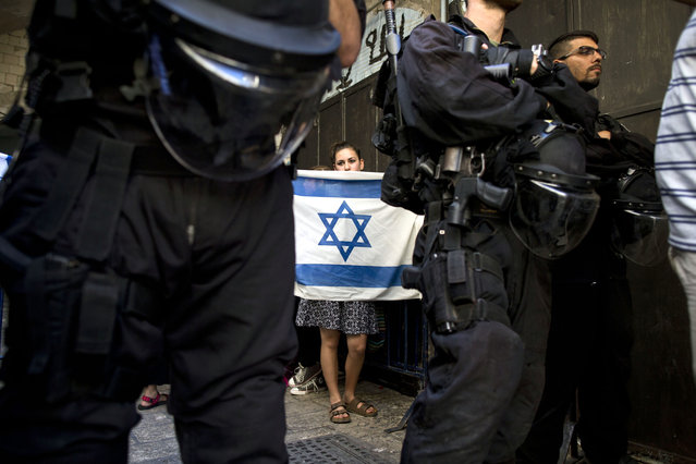 """Israeli border police stand guard as a right-wing Jewish girl from the """"Students for the Temple Mount"""" movement holds an Israeli flag at the entrance to the Al-Aqsa mosque compound in the Old city of Jerusalem, Israel, August 9, 2015. Tension escalates at the al-Aqsa compound as more Jewish right-wing extremists are trying to pray inside the compound. The area houses the mosque, considered the third-holiest site in Islam, but it is also the site of the ruins of the biblical Jewish temple and is the most sacred site in Judaism. (Photo by Abir Sultan/EPA)"""