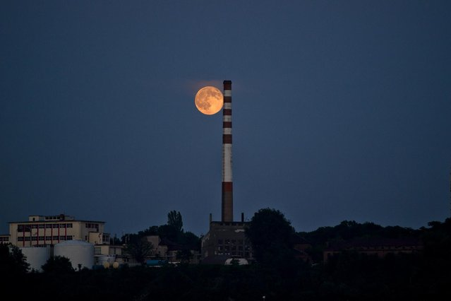 """A perigee moon, known as a supermoon appears above the Bulgarian-Romanian border in Giurgiu, Romania, Saturday, July 12, 2014. The phenomenon, which scientists call a """"perigee moon"""", occurs when the moon is near the horizon and appears larger and brighter than other full moons. (Photo by Vadim Ghirda/AP Photo)"""