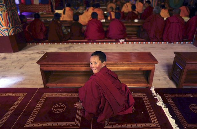 A young Tibetan monk smiles inside a Buddhist temple in Dege county of Garze Tibetan Autonomous Prefecture, Sichuan province, China, July 24, 2015. (Photo by Reuters/China Daily)