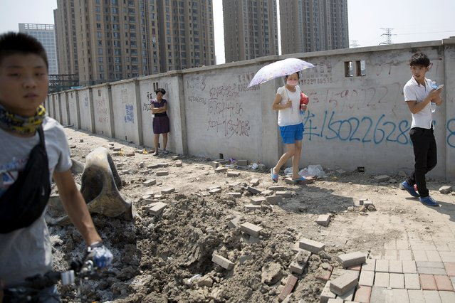 People evacuated from residential area look at debris that landed and damaged the road about two kilometres from the explosion site in Binhai new district in Tianjin, China August 13, 2015. (Photo by Damir Sagolj/Reuters)