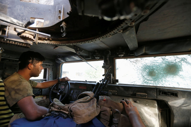 A member of Iraqi counterterrorism forces drives in a military vehicle in Falluja, Iraq, June 26, 2016. (Photo by Thaier Al-Sudani/Reuters)