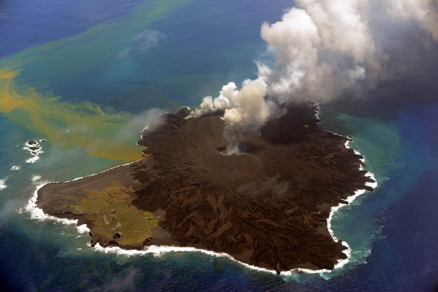 This handout picture taken by Japan Coast Guard on July 23, 2014 shows the newly created islet (R) and Nishinoshima island (L), which are conjoined with erupting lava at the Ogasawara island chain, 1,000 kilometres south of Tokyo. A smouldering islet off Japan's Pacific coast has grown six times in its land surface since before it merged last December with a landmass created by volcanic eruptions. (Photo by AFP Photo/Japan Coast Guard)