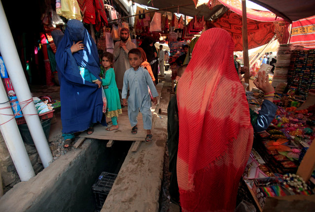 An Afghan woman, clad in a burqa, shops at a market in Peshawar, Pakistan June 29, 2016. (Photo by Fayyaz Hussain/Reuters)