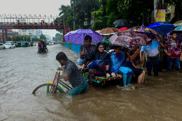Bangladeshi commuters use a rickshaw to cross a flooded street amid heavy rainfall in Dhaka on July 26, 2017. Bangladesh is experiencing downpours following a depression forming in the Bay of Bengal. (Photo by Munir Uz Zaman/AFP Photo)