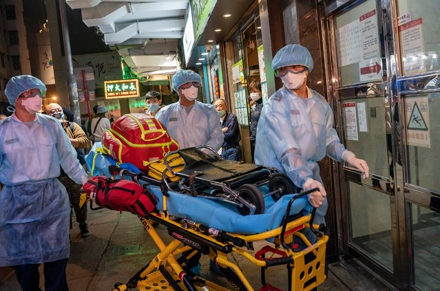 """Paramedics wearing personal protective equipment carry a stretcher into a residential building at North Point district on February 23, 2020 in Hong Kong, China. South Korea has raised the Wuhan Covid-19 virus alert to the """"highest level"""" as confirmed case numbers keep rising. Four more people in Hong Kong were confirmed to have contracted with coronavirus, including two elderly women who recently visited a North Point Buddhist worship hall, bringing the total tally of cases in the city to 74. (Photo by Anthony Kwan/Getty Images)"""