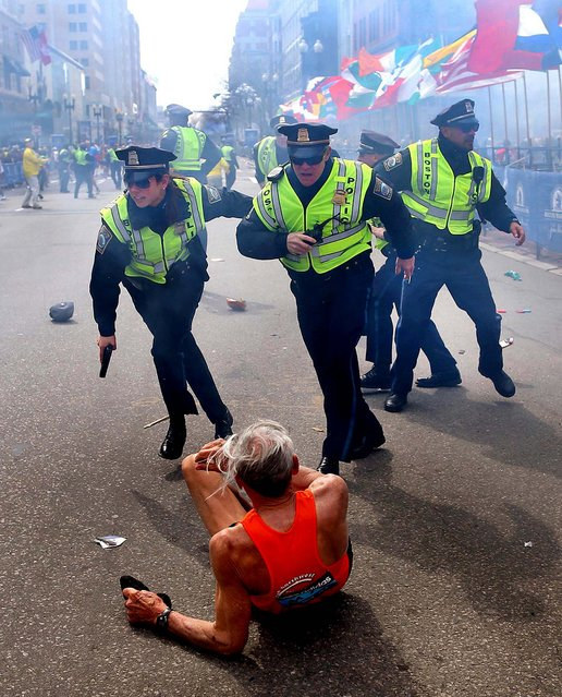 First Place, Domestic News. Photo by John Tlumacki of The Boston Globe, who was also named Photojournalist Of The Year (Large Markets). Boston police officers race toward downed runner Bill Iffrig seconds after the first bomb exploded during the April 15, 2013, Boston Marathon. (Photo by John Tlumacki)