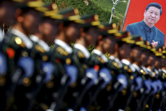 A picture of Chinese President Xi Jinping is seen behind soldiers of China's People's Liberation Army marching during a training session for a military parade to mark the 70th anniversary of the end of the World War Two, at a military base in Beijing, China, August 22, 2015. (Photo by Damir Sagolj/Reuters)